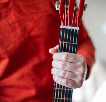 Close-up of a guitar player or a person learning to play an acoustic guitar. Home learning to play a musical instrument 免版税图像