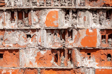 Old red brick wall. The bricks are laid in rows. Grunge stone texture. High quality photo