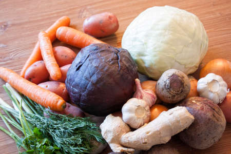 Set of vegetables cabbage potatoes carrots onion garlic parsley dill beet ginger on a wooden table background