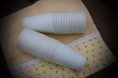 A stack of plastic cups on the background of a wooden table