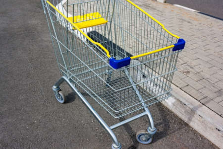 empty Yellow blue silver shopping cart against grey background with white paint lines, shopping trolley against grey asphalt