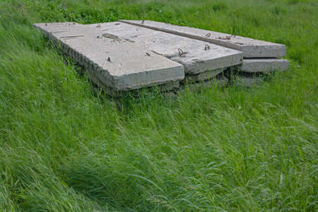 Stack of concrete blocks on a background of green grass construction site Stock Photo