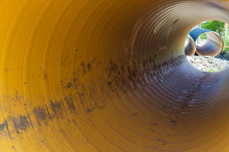 View inside of long plastic tube under ground. Tunnel under ground with far light