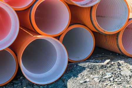 Pipes of PVC large diameter orange color prepared for laying on construction site