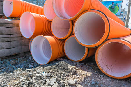 untruth: Pipes of PVC large diameter orange color prepared for laying on construction site