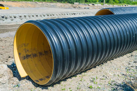 Pipes of PVC large diameter prepared for laying on construction site