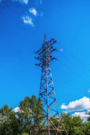 electric grid: Supports high-voltage power lines against the blue sky. Electrical industry.