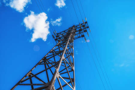 Supports high-voltage power lines against the blue sky. Electrical industry.