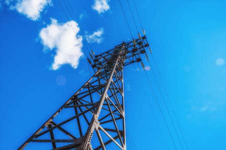Unterstützt Hochspannungsleitungen gegen den blauen Himmel. Elektroindustrie.