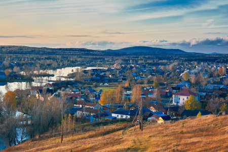 View of the village of Chernoistochinsk Sverdlovsk region from the top of the mountain at sunset in autumn