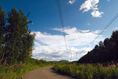 Supports high-voltage power lines against the blue sky with clouds. Electrical industry. Stock Photo