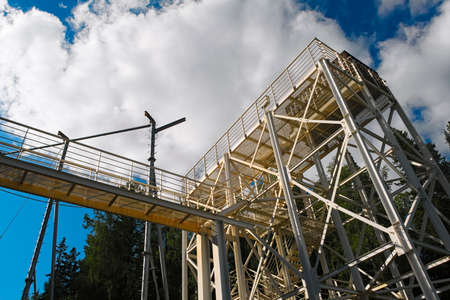 Metal structures of a large ski jumping-off against the sky and clouds