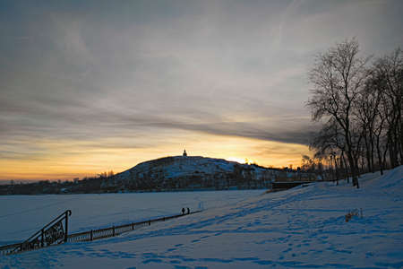 Winter landscape with snowy field, leafless trees and frozen lake in city park. Banque d'images