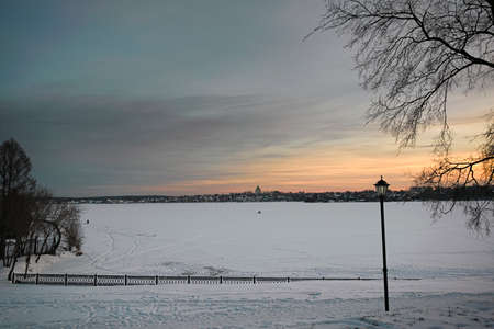 Winter landscape with snowy field, leafless trees and frozen lake in city park. Stock Photo