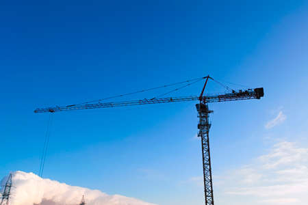 Tower crane on sunset background