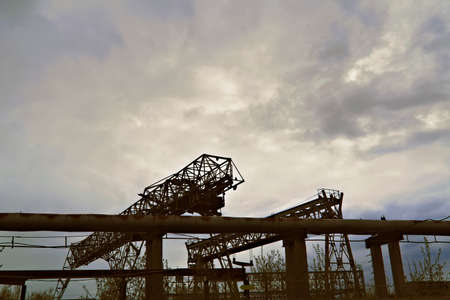 Bridge cranes in a factory against a cloudy sky background