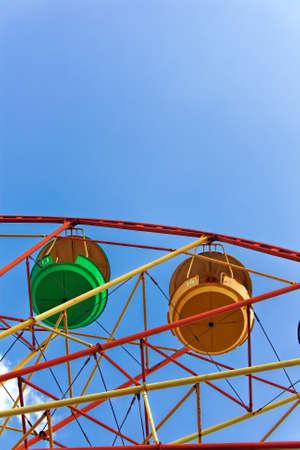 Ferris wheel against the blue summer sky in the city park