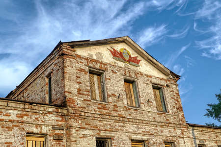 An old abandoned brick building with the emblem of the USSR