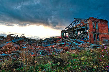 The ruins of a destroyed building in the city against the backdrop of a dramatic autumn sunset sky