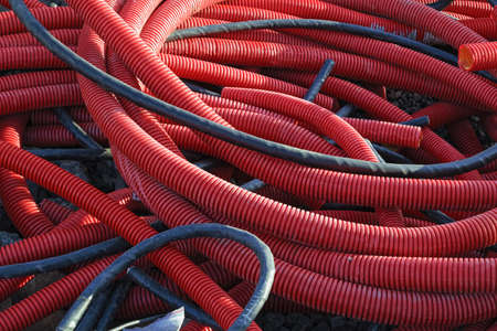 Red PVC corrugated pipes for cable lay on the construction site