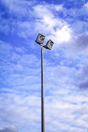 Sport field lighting outdoor floodlight straight on angle against blue sky Imagens