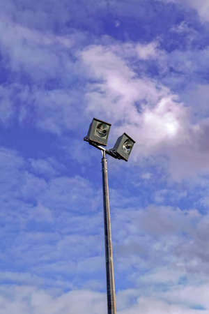 Sport field lighting outdoor floodlight straight on angle against blue sky Stock Photo