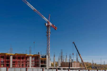 Bau eines Einkaufszentrums Kräne auf einem Hintergrund des blauen Sommerhimmels Standard-Bild