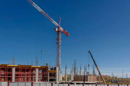 Construction of a mall cranes on a background of blue summer sky 版權商用圖片 - 113006628