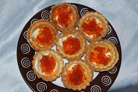 Tartlets with red caviar close up. Close-up salmon caviar. Delicatessen. Gourmet food. Texture of caviar. Seafood. Archivio Fotografico