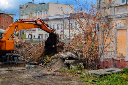 excavator at a construction site for the restoration of old urban buildings Stock Photo