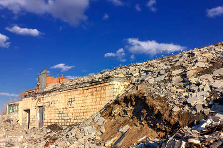 The ruins of a destroyed building in the city against the backdrop of a blue sky. Dual-ISO photo.