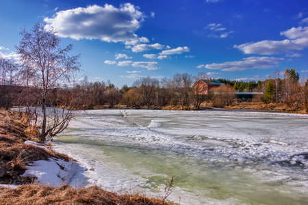 Spring landscape melts ice on a small river at the edge of the village.