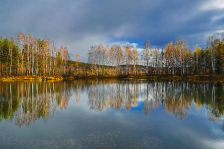 Beautiful autumn forest with colorful trees and pacturesque sky reflected in the water. Autumn nature landscape.