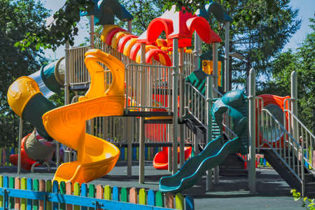 Empty playground in a city park on a hot sunny summer day. Stock Photo