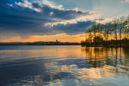 Dramatic sunset on the banks of the city pond. Spring landscape.