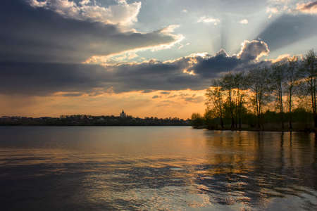 Dramatic sunset on the banks of the city pond.