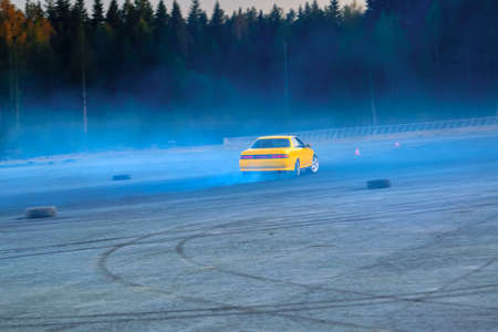 Blurred of image diffusion race drift car with lots of smoke from burning tires on speed track.