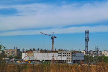 Construction of a mall cranes on a background of blue summer sky