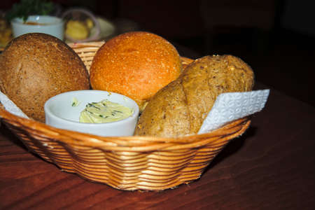 Delicious, freshly baked bread of various assortment in a straw basket. Stock Photo