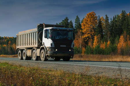 A truck carries goods along a forest road against the backdrop of an autumn forest and blue sky .