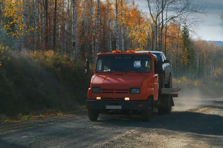 Tow truck rides along a forest road against the backdrop of an autumn forest. Help on road transports wrecker broken car.