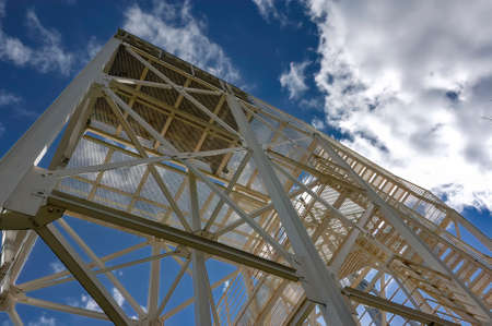Industrial construction. Metal structures against the blue sky and white clouds.