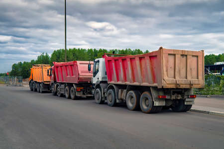Lorries dump trucks at a construction site are waiting in line for loading.