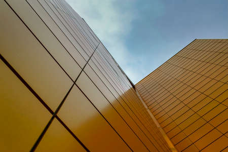 Wall of a high-rise building faced with yellow tiles against the sky. Bottom view.