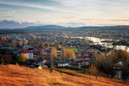 View of the village of Chernoistochinsk Sverdlovsk region from the top of the mountain at sunset in autumn.