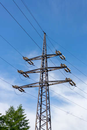 Electrical concrete pole. Power pole on a background of blue sky with white clouds.