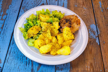 Potatoes, lettuce and a cutlet of turkey meat on a white dish on a background of wooden table.