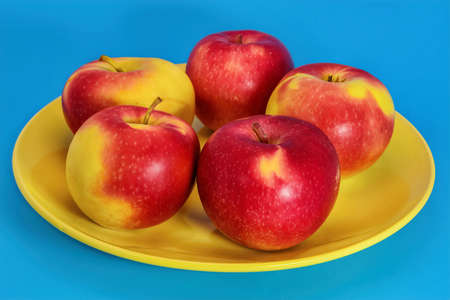 Close up of ripe red apples in a bowl on blue background.