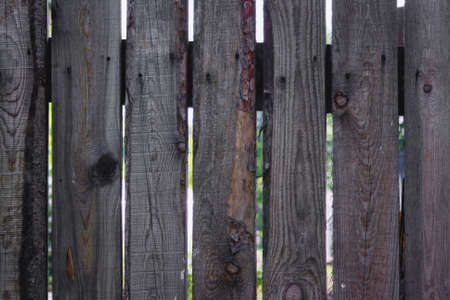 The texture of the boards of an old wooden fence closeup. Close up of gray wooden fence panels.