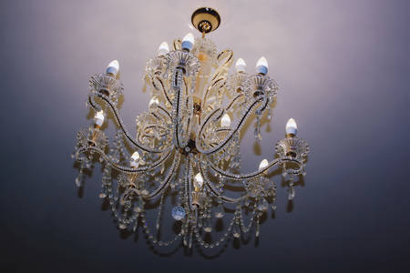 Crystal chandelier hanging on ceiling. Beautiful magnificent chandelier on the ceiling. Closeup.